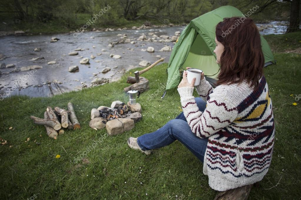 Girl sitting near a campfire at the campsite looking at map and drinking coffee.