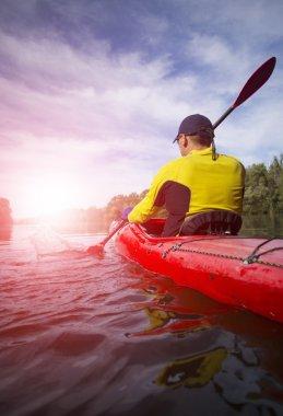 A man paddles a red kayak.