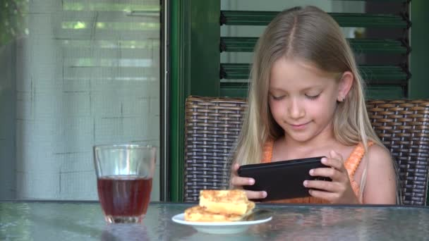 Girl Playing Smartphone while Eating Breakfast, Kid Browsing Internet on Phone, Child Reading Messages Searching Online on Devices
