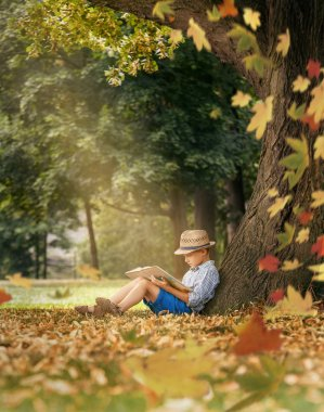 Boy with book sitting under tree