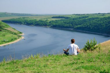 Man sits on the top a hill viewing wide Dnister river. Yoga medi