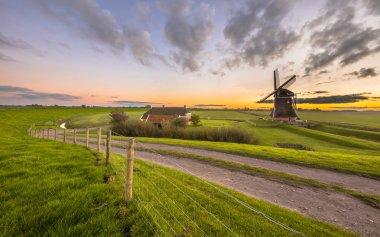 Dutch Wooden windmill in flat grassy landscape