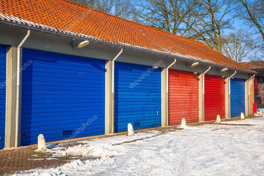Garage Doors In In Blue And Red Next To Each Other On A Snowy Wi
