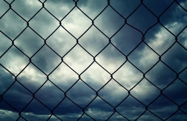 Wire fence closeup with dark cloudscape background