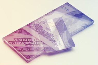 Double exposure: Credit card on hundres dollar bills closeup