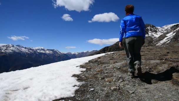 Dva turisté chůzi na horský hřeben a stojí před malebnou krajinu