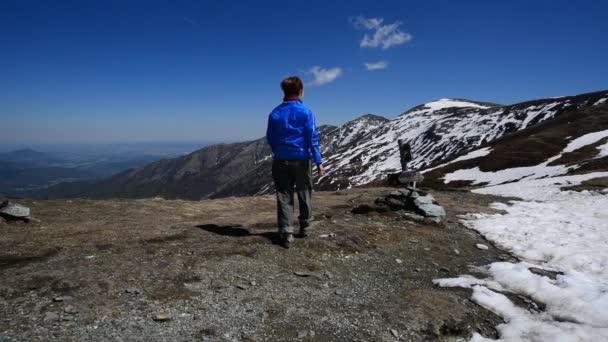 Tramp chůzi na horský hřeben a stojí před malebnou krajinu
