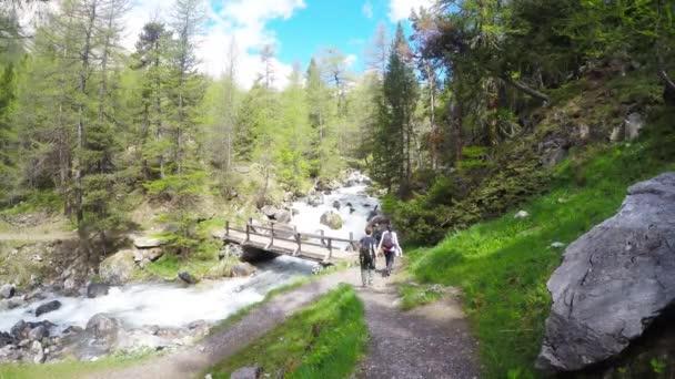 Batůžkáři, turistika ve svěží zelené údolí s divoký proud. Letní dobrodružství a průzkumu v italských Alpách