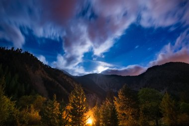 The starry sky with blurred motion clouds and bright moonlight, captured from larch tree woodland, glowing by burning fire. Expansive night landscape in the European Alps. Concept of adventure into th