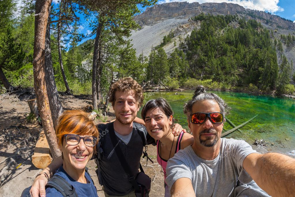 Four young people taking selfie in idyllic landscape with green lake, conifer woodland and mountains in background. Scenic fisheye distortion. Concept of traveling people and nature beauty exploration.