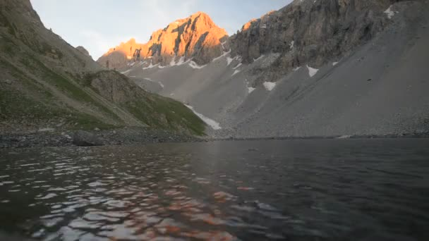High altitude alpine lake in dramatic rocky landscape. Expansive view of mountain peak glowing at sunset.