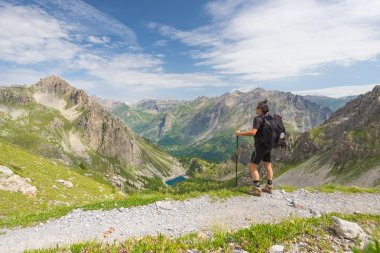 Backpacker hiking on footpath and looking at expansive view from the top. Summer adventures and exploration on the Italian French Alps.