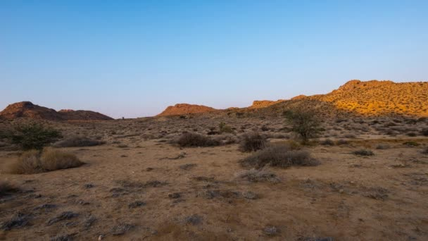 Colorful sunrise over the Namib desert, Aus, Namibia, Africa. Clear sky, glowing rocks and hills, time lapse video.