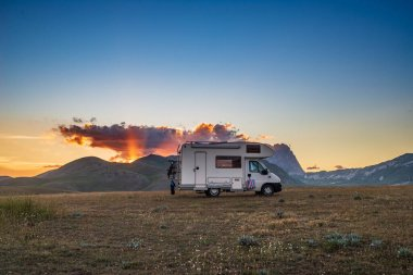 Campo Imperatore Highlands, Abruzzo, İtalya 'da kamp minibüsünün üzerinde gün batımı dramatik gökyüzü. Eşsiz dağların ve kayalık dağların üzerindeki destansı bulutlar alternatif vanlife tatil konsepti..