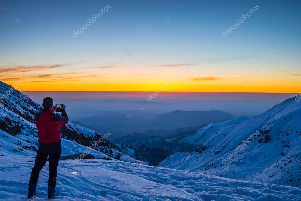 Alpinist taking selfie at twilight