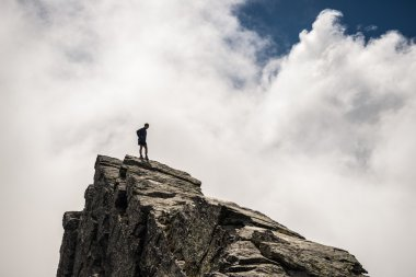 Hiker standing high up on rocky mountain peak
