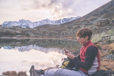 Checking smartphone on scenic mountains