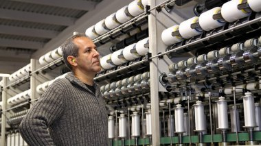 Engineer is Looking at the Machines in Textile Factory