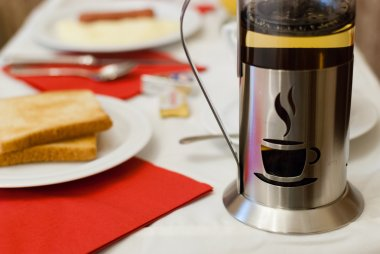 French press filled with coffee on a breakfast table