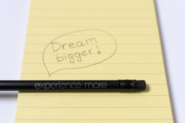 Black pencil with a message on a yellow notepad