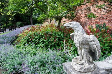 Eagle sculpture in a garden full of flowers