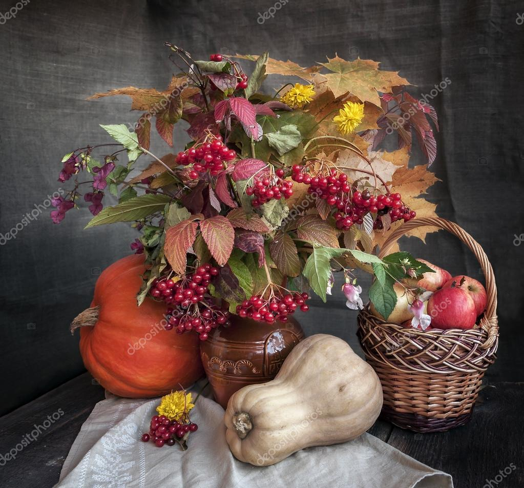 The autumn bouquet of leaves, flowers and fruits on a wooden table