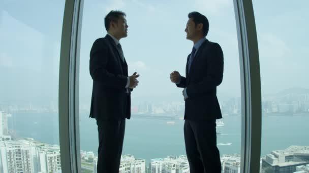 Asian businessmen meeting in modern boardroom