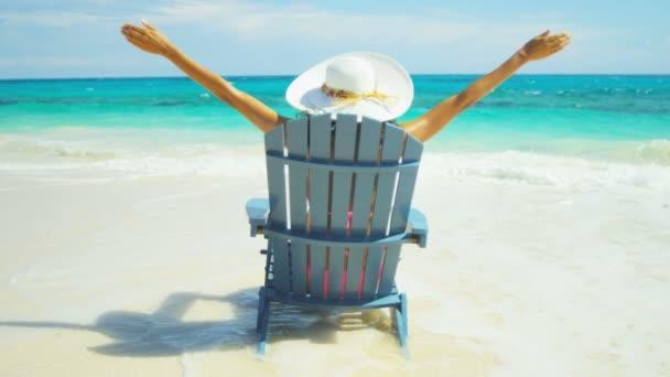 fából készült szék trópusi strandon napozó lány