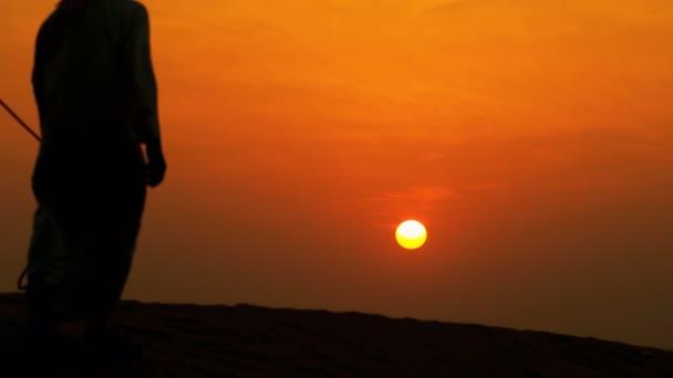 man leading his camels through desert