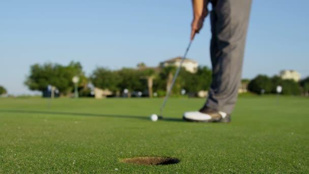 golfista holing jeho míč