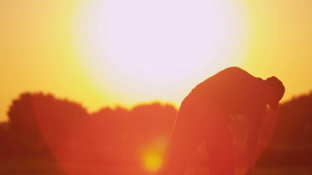 männliche Golfspieler Golfen bei Sonnenuntergang