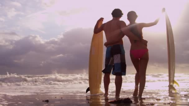 Couple with surfboards on beach