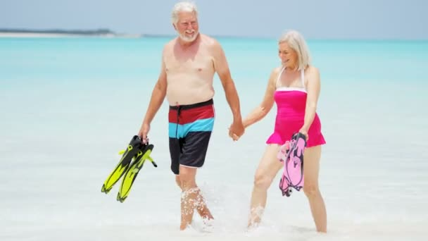 senior couple with snorkeling equipment on beach