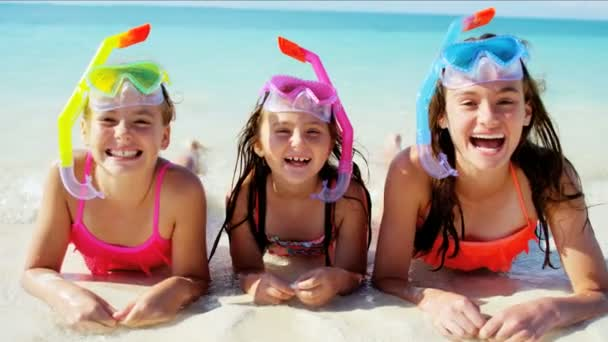 Caucasian sisters with snorkels on beach vacation