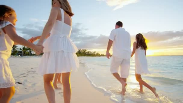 Caucasian family walking on sandy beach