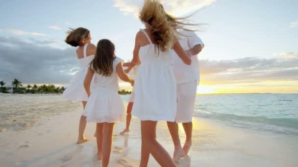 Caucasian family enjoying beach vacation at sunset