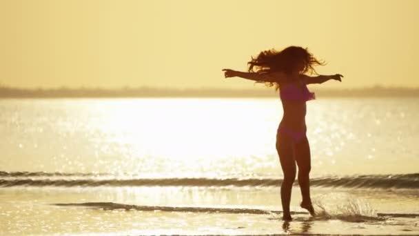 Čínská dívka v bikinách tančí na pláži