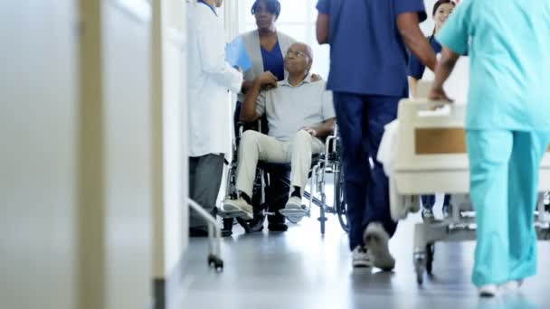 man on wheelchair with wife consults with doctor
