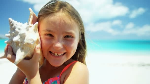 little girl on a beach holding a conch shell