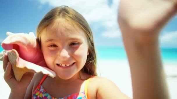 Bambina su una spiaggia che tiene lle coperture della Conca