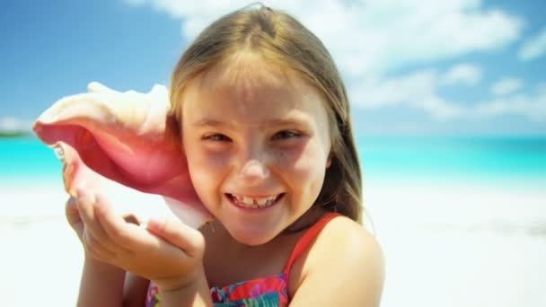 holčička na pláži drží lastura