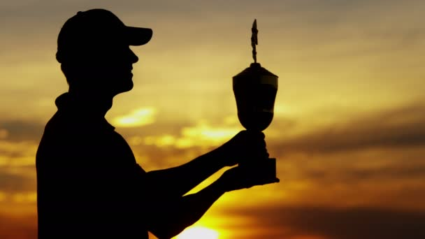 silhouette of professional golf player with trophy