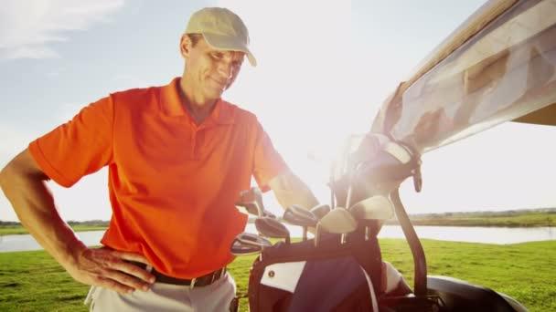 profesionální mužské golfové hráče a golfový vozík s vybavením