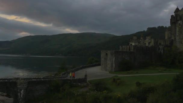 Eilean Donan castle za soumraku s lidmi