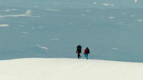 Kletterer, die Überquerung einer Schnees bedeckt Bergkette