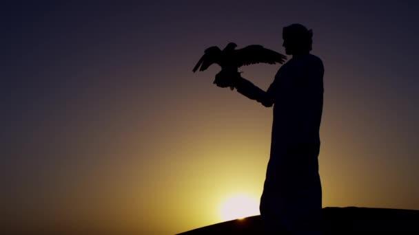 uomo con rapace sulle sabbie del deserto