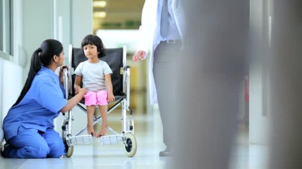 Pediatrician and nurse cheering up girl