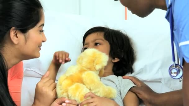 Girl clutching teddy bear in hospital bed