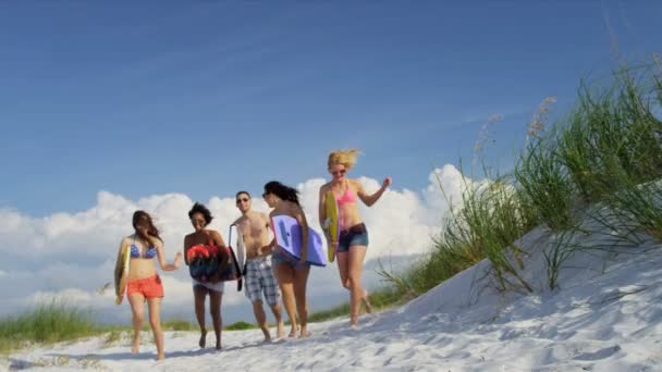 Teenagers carrying body boards across beach