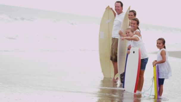 Family with bodyboards watching waves